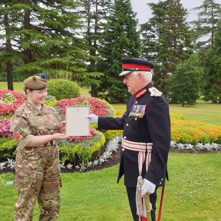 Cpl Young left receiving her certificate of appointment from the Lord Lieutenant of Moray Major General Seymour Munro